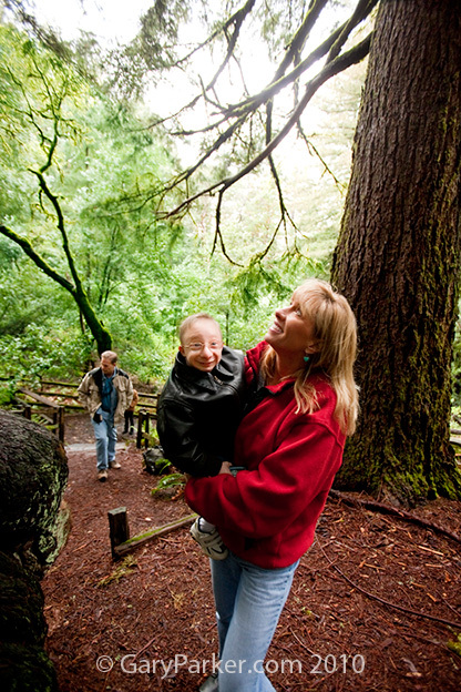 Shelly holds 18 year old Nick during a walk through the redwoods as his Dad, Lawrence, follows.