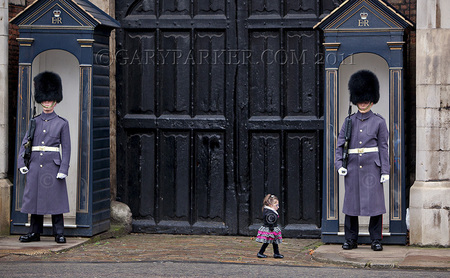 "Bridgette Jordan, 22, a 19 pound college cheerleader & America's Shortest Lady at under 27"" tall, succeeds in unnerving the steely-eyed gaze of the Queen's Guards at Buckingham Palace, during a recent trip to London."