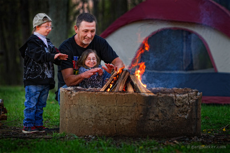 Scott Jordan, with his children Bri and  Brad Jordan, warm themselves during a camping trip. Primordial Dwarfism